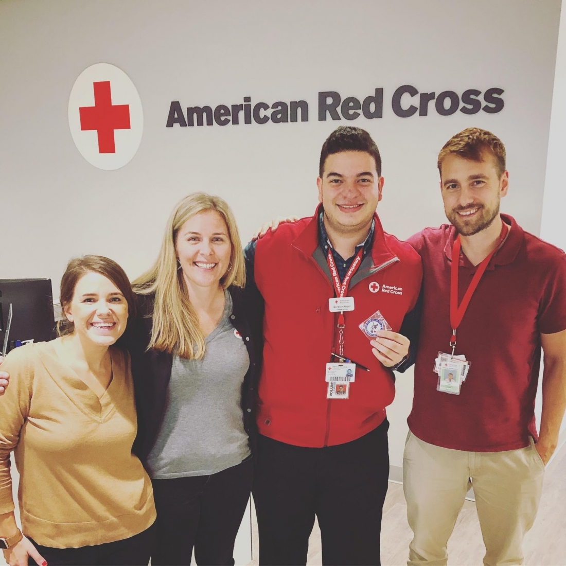 "A group of four people posing for a photo in front of an ""American Red Cross"" logo."