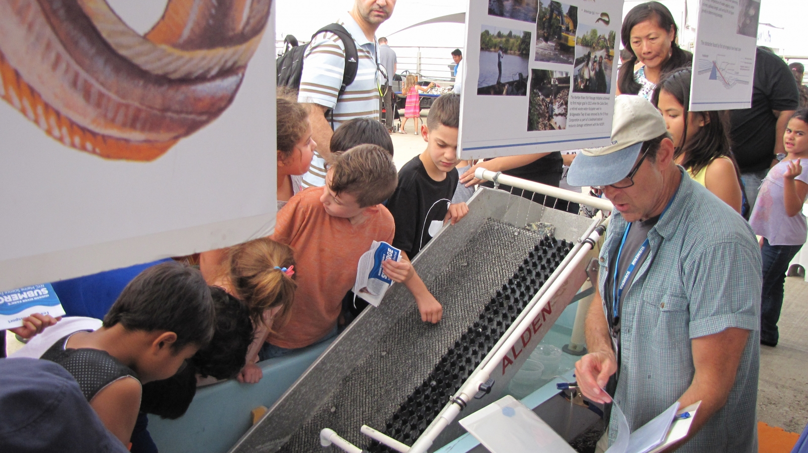 A group of people around a demonstration table with an eel ladder.