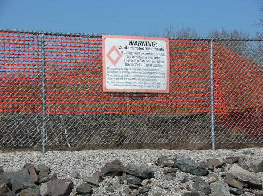 "A sign on a sign warning of ""contaminated sediments."""