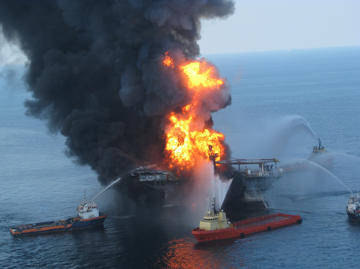 Several vessels pump pressurized water at a fire on an oil rig.