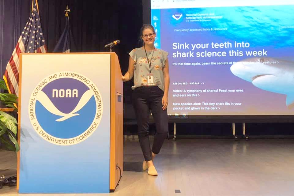 A girl standing next to a podium with a NOAA logo on it.