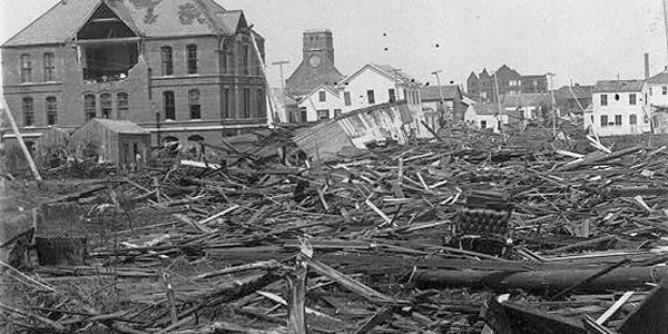 A black and white photo of a street with collapsed and demolished buildings.