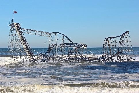 A damaged roller coaster surrounded by water.