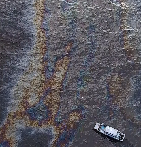 An aerial image of a boat near an oil sheen.