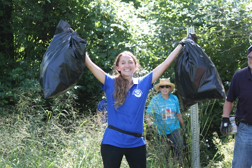 A girl holding up two trash bags.
