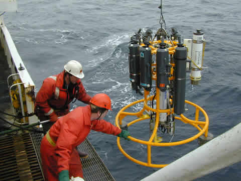 Two men pulling a scientific instrument aboard a vessel.
