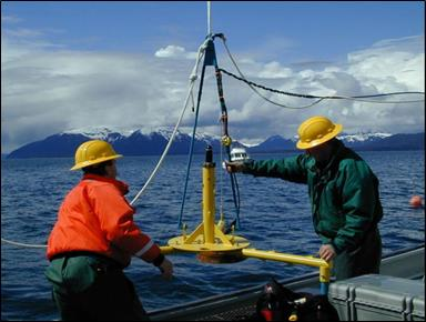 Two people on a vessel lowering an instrument into the water.