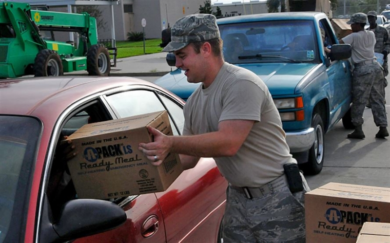 A man in military uniform handing a box to a person in a vehicle.