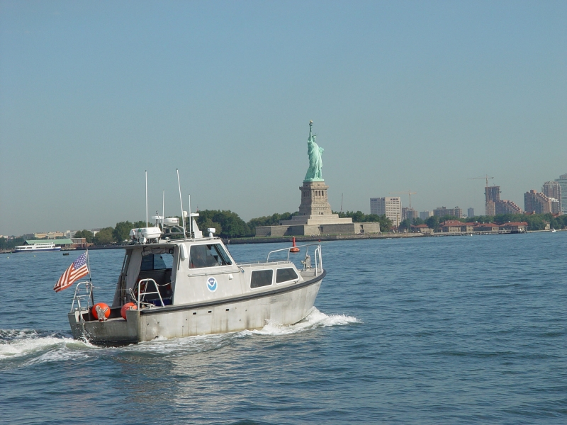 A boat in a body of water with the Statue of Liberty in the background.