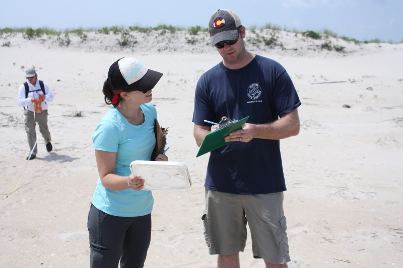 Two people on a beach looking at clipboards.