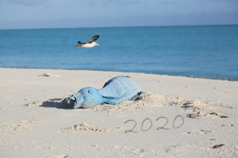 "A toy on a beach with ""2020"" written in the sand."