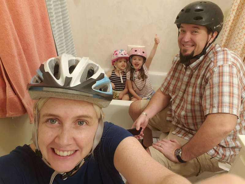 A family of four all wearing helmets with two children in a bathtub.