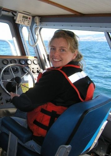 A woman in a life jacket steering a boat.
