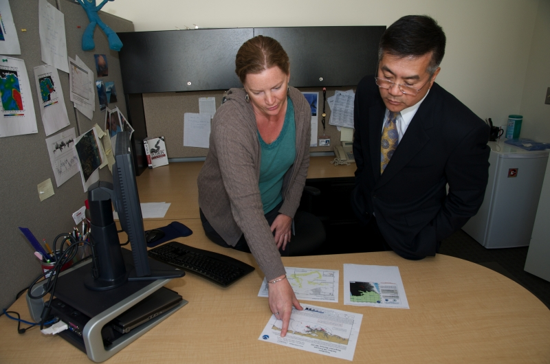 A woman in an office pointing to a piece of paper as she talks to a man.