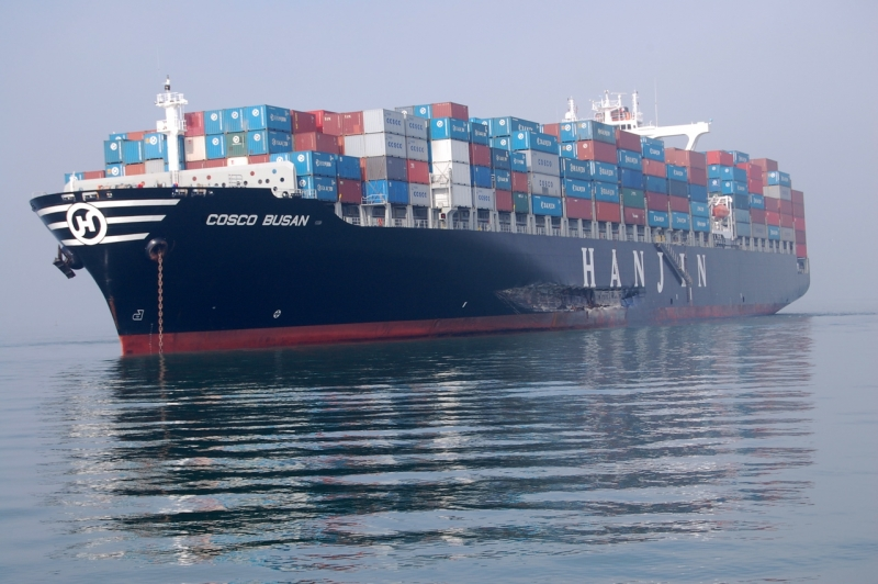 "A large shipping vessel loaded with containers. A gash appears on the port side over the text ""Hanjin."""