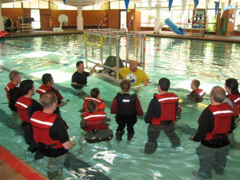 People in a pool wearing safety gear.