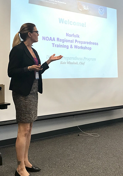 "A woman standing in front of a projector screen that reads ""Norfolk NOAA Regional Preparedness Workshop and Training."""