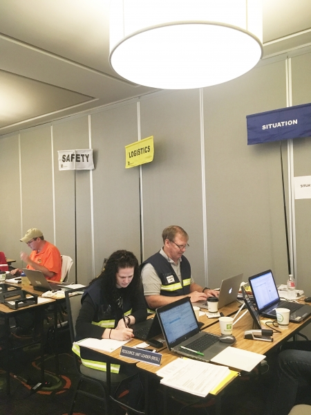 "People on computers sitting at desk under signs that read ""Safety,"" ""Logistics,"" and ""Situation."""