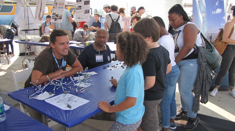 A group of kids at a table with molecule models talking to two NOAA staff.