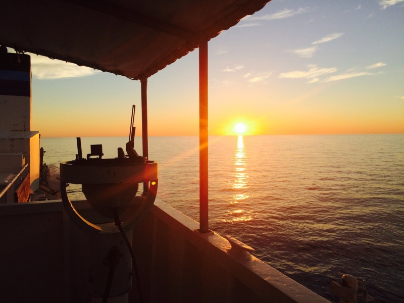 A sunrise as seen from a vessel on water.