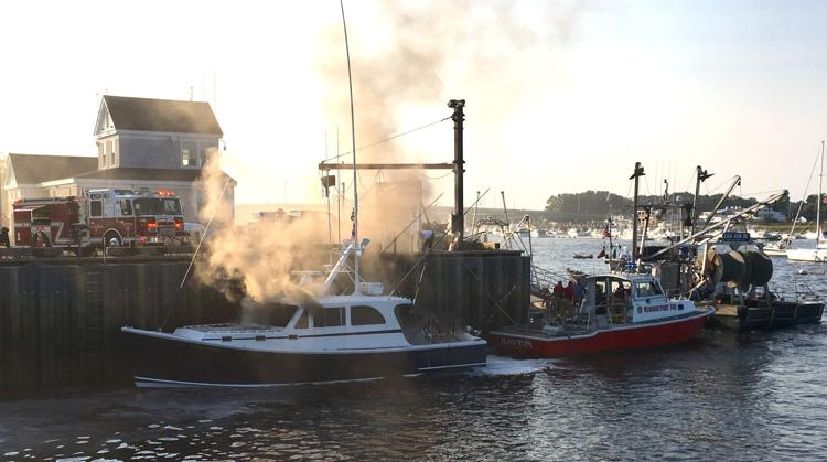 Smoke rising from a vessel at a dock.