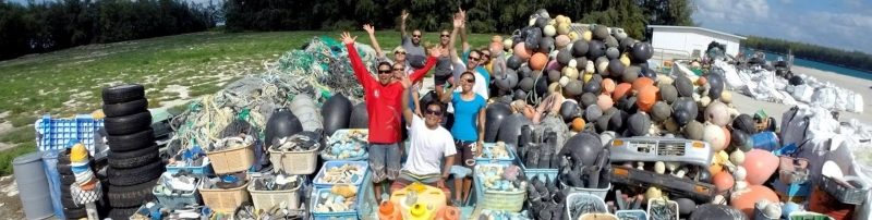 A group of people surrounded by a large trash pile.