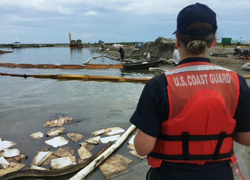A person in a U.S. Coast Guard life preserver overseeing cleanup.