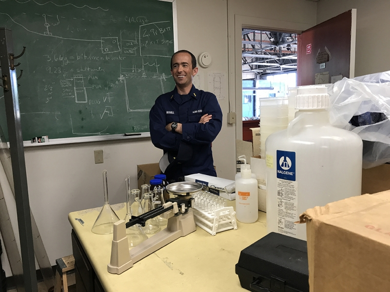 A man standing in a lab with a chalkboard in the background.