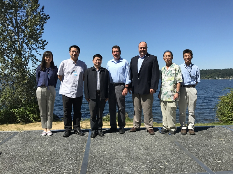 Seven people pose together for a photo in front of Lake Washington.