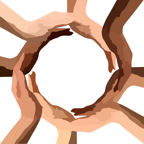 An image depicting a circle of hands of different colors creating a globe-like shape.