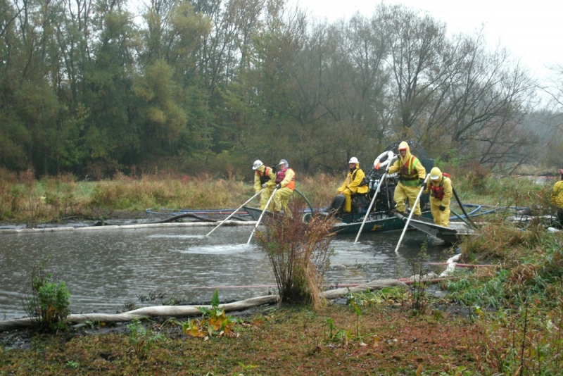 Workers spraying sediment with water.