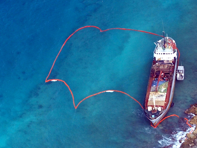 An aerial view of a grounded ship with pollution boom surrounding it.