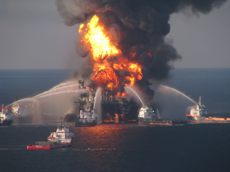 Several vessels pumping pressurized water on an oil platform on fire.
