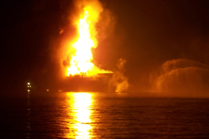 A dark and blurry image of an oil platform on fire.