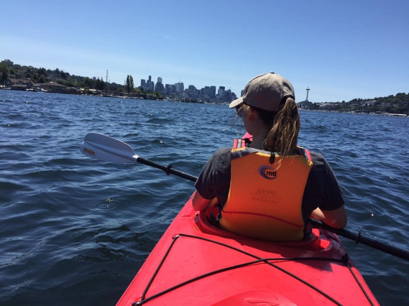 A girl in a kayak with a city skyline in the background.