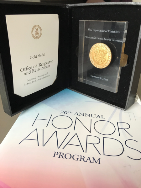 "A photo of an award that reads ""Gold Medal Office of Response and Restoration"" on a table with a paper reading ""70th Annual Honors Awards Program."""