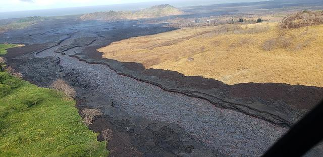 An aerial view of a river of black lava.