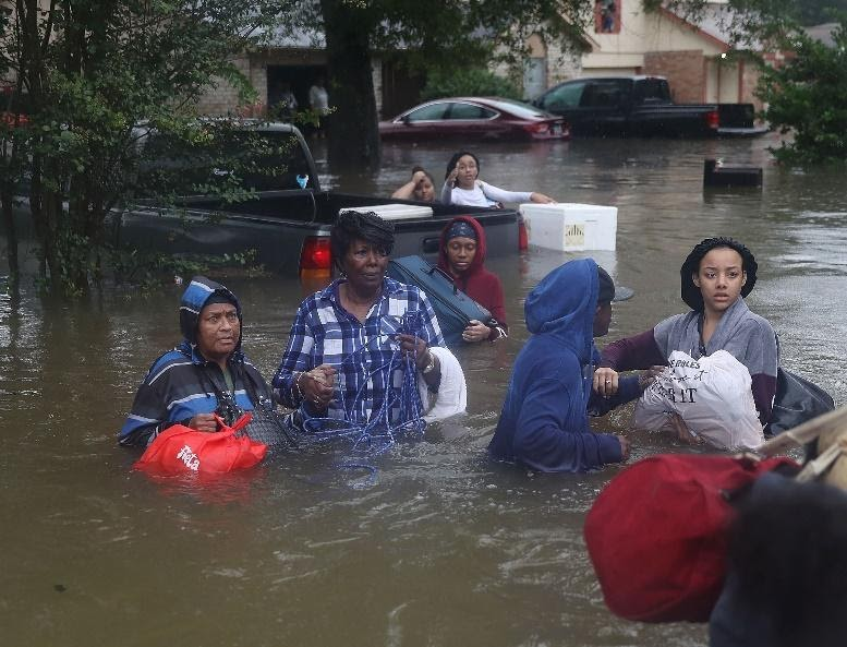 People moving through flood waters.