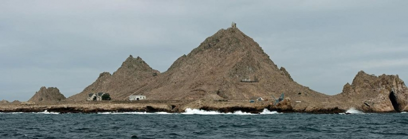 A rocky island with three buildings visible.