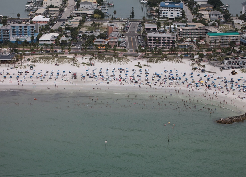An aerial view of a beach with people on it and a city in the background.
