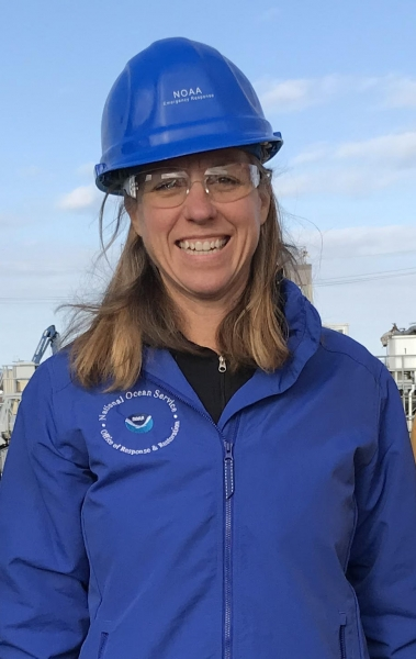 A photo of a woman wearing a hard hat and a blue jacket with the National Ocean Service logo on it.