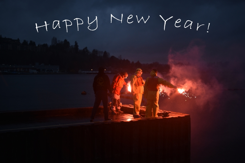 "People in orange response gear standing on a dock holding flares. Above, the image reads ""Happy New Year!"""