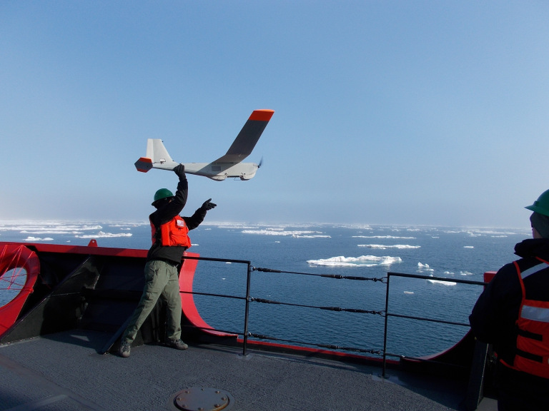 A man launching an unmanned aerial vehicle, or drone, from the bow of a vessel.
