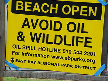 A sign warning people of oil on a beach.