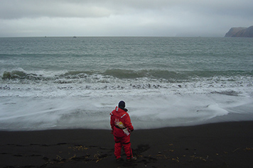 A person in orange gear standing on a beach looking out at the water.