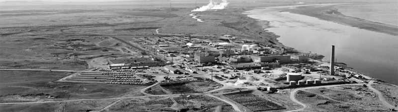 A black and white image of an industrial site on a river.