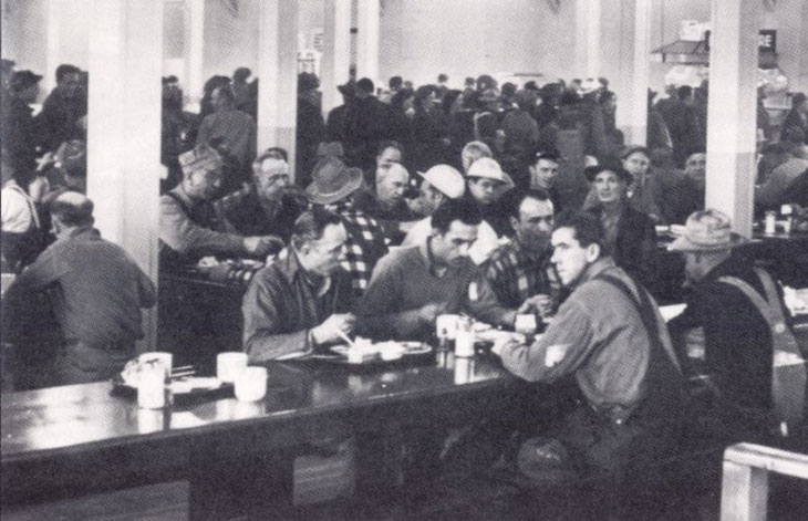 A black and white photo of workers in a cafeteria.