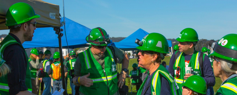 A group of people in green hard hats and reflective vests.