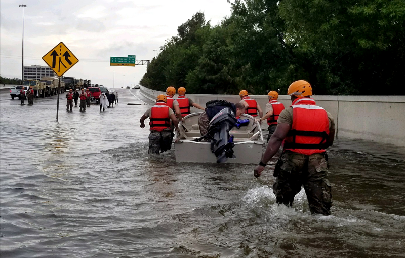 A group of people walking through a flooded highway with a boat.