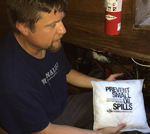 "A man holding up an absorbent oil spill prevention kit pillow that reads, ""Prevent small oil spills."""